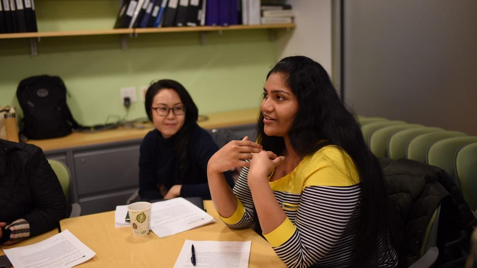 An MA student speaking while seated at a conference room table.