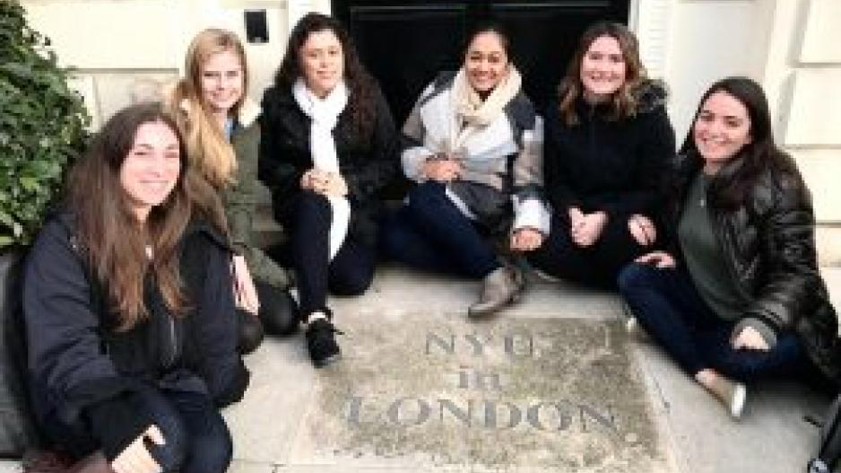 "Students sitting around a plaque that reads ""NYU in London"""
