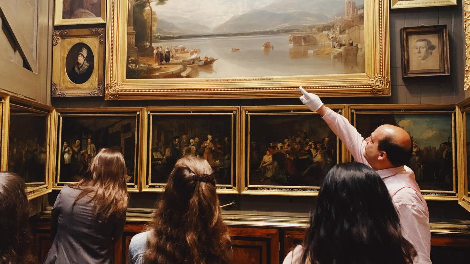 Professor pointing at painting.