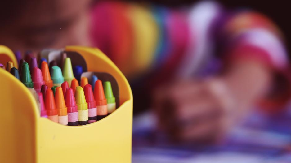 Crayons with a coloring child in the backgroun