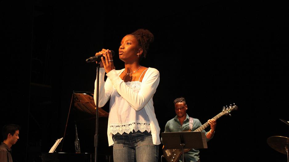 Singer onstage with piano and guitar accompanists behind her