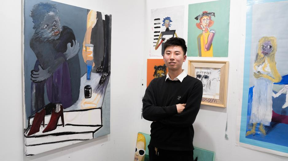 Student in his studio with paintings on wall.