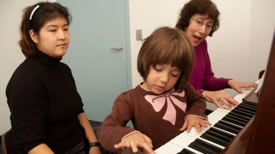 Child at Piano with Music Therapist