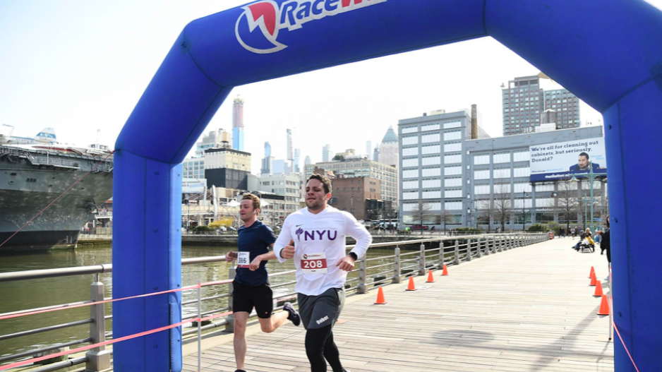 Two students crossing the finish line of a 5k, with one wearing a white NYU shirt.