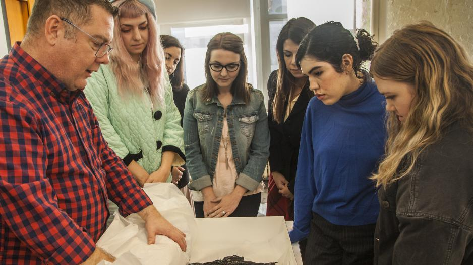 Students looking at textile in class
