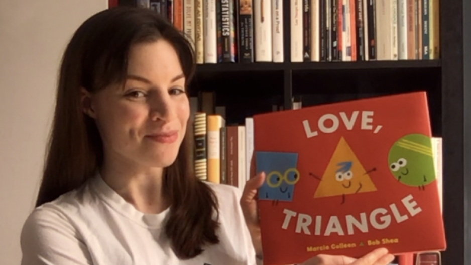 "Dr. Moira Dillon holding up a book called ""Love, Triangle"" to read"