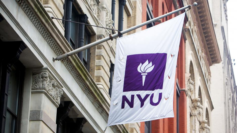 The NYU flag flying from the side of a building