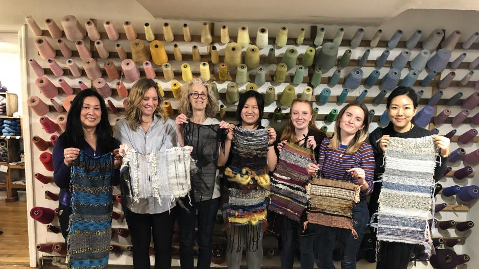 Students with weaving in front of wall of thread.