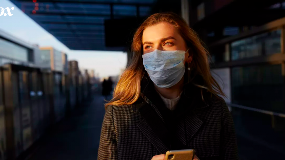 Women with mask on face on subway platform.