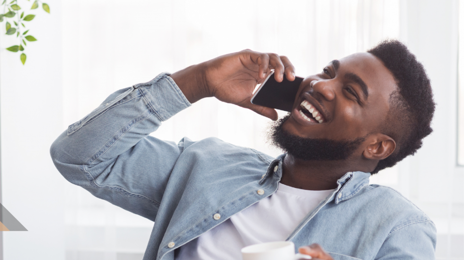 A man on phone holding a cup and laughing