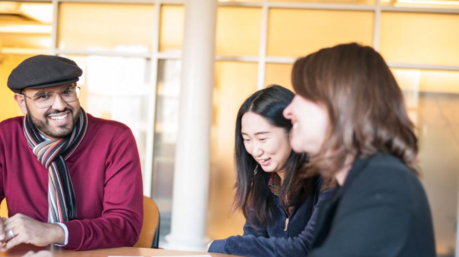 Two international students speaking with an adviser