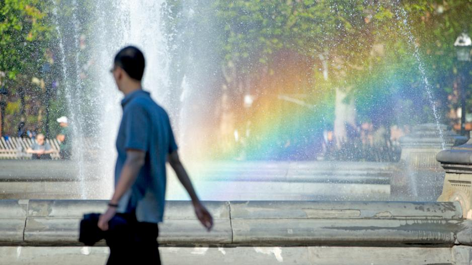 A rainbow appears in the Washington Square fountain as a student passes by