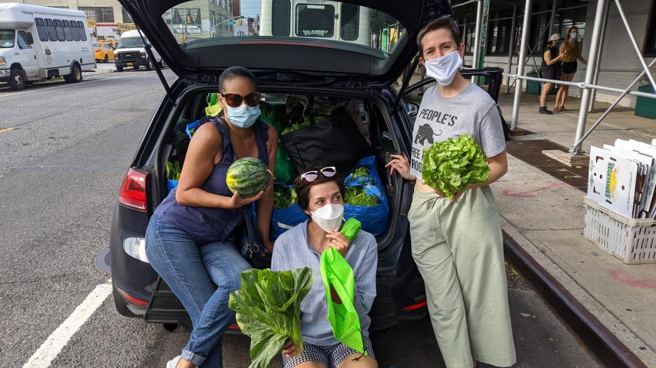 Leah and two other community members holding produce and posing in front of the open trunk of a car.