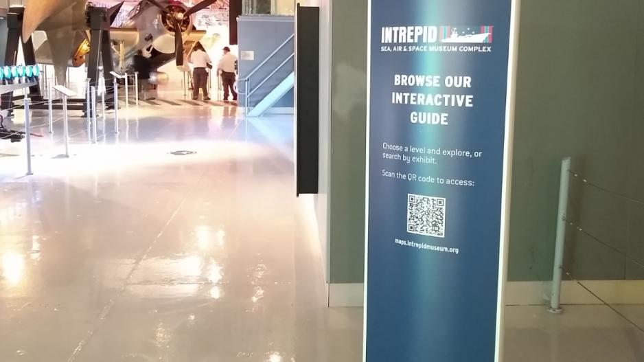 A sign at the Intrepid Museum with a QR code for access to an interactive museum guide.