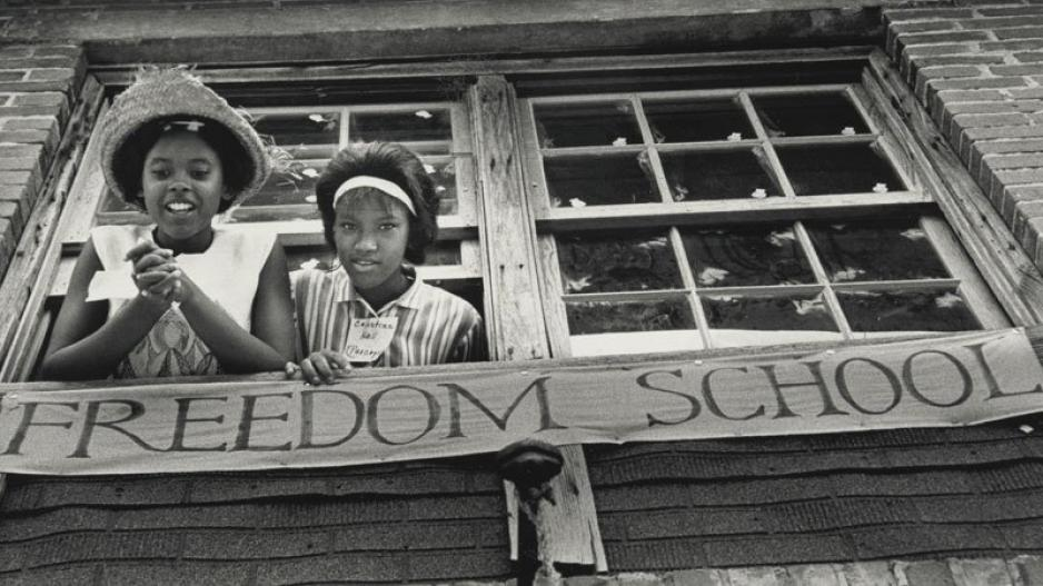 Two young black girls smile and lean out of the window of a freedom school