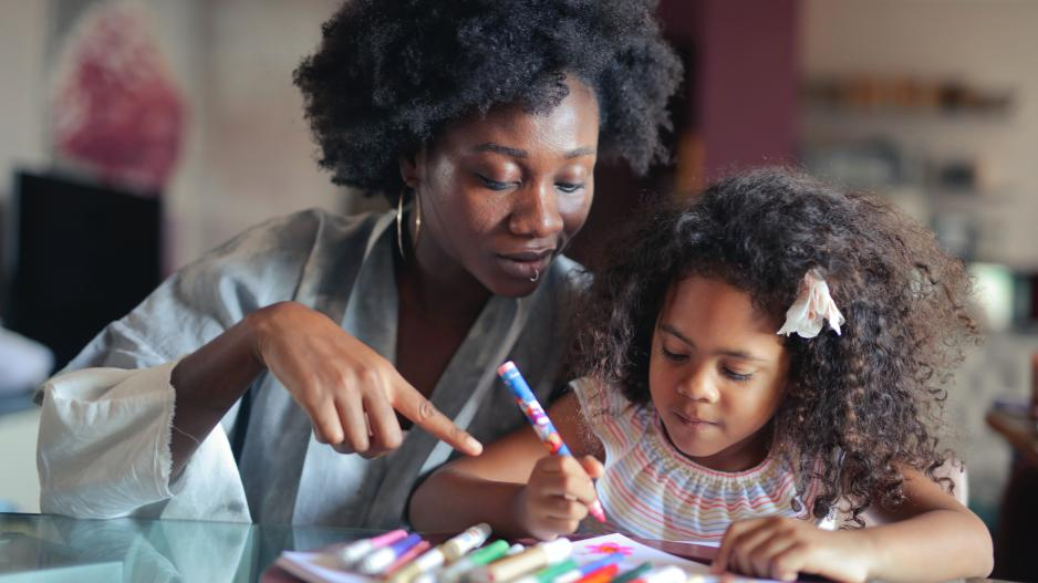 A Black mother and daughter sit together as the daughter colors