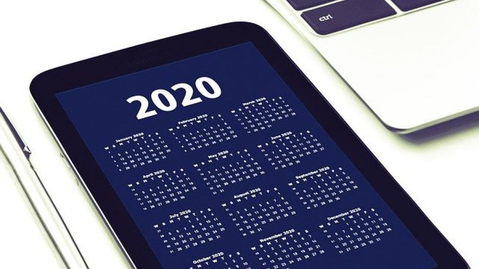 "A tablet showing a screen with the header ""2020"" followed by a monthly calendar for the year."
