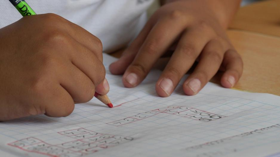 Student completing math problems on grid paper