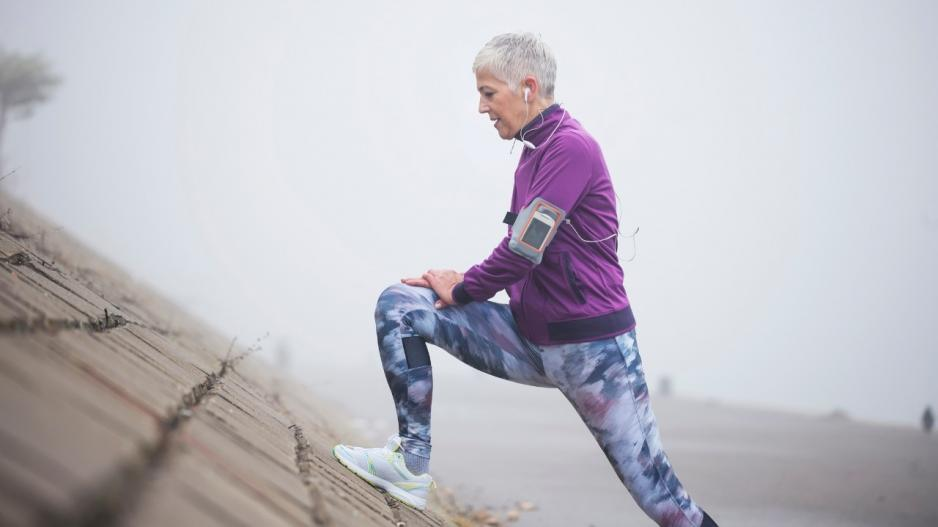 An older woman with short white hair in exercise clothes stretching one leg by leaning against an inclined surface.