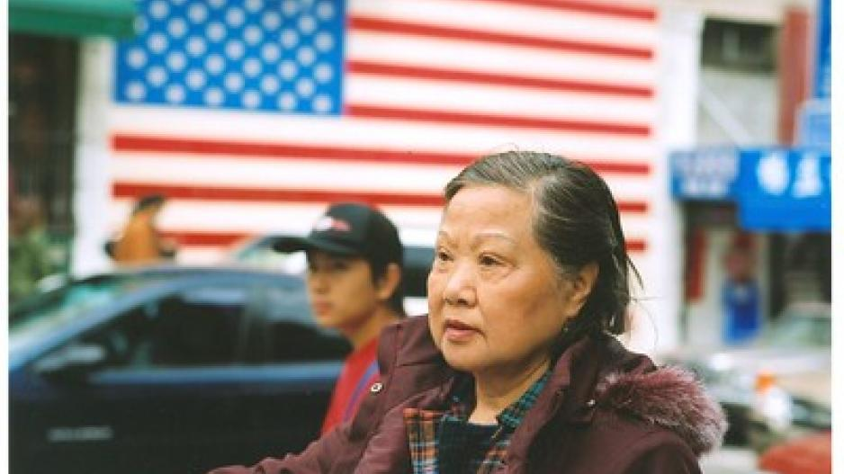 An older Asian woman stands at the forefront with a younger Asian boy and an American flag in the background