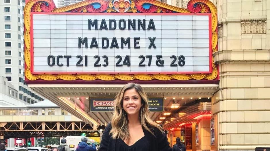 "Brittney posing in front of a marquee that reads ""Madonna Madame X Oct 21 23 24 27 & 28"""