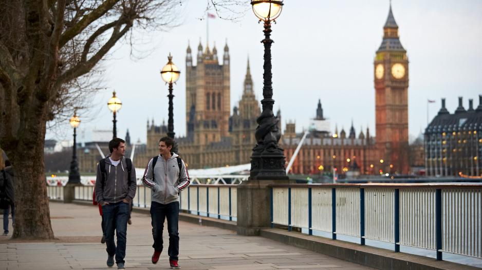 An image of NYU student walking down The Queen's Walk by River Thames with Big Ben in the background.