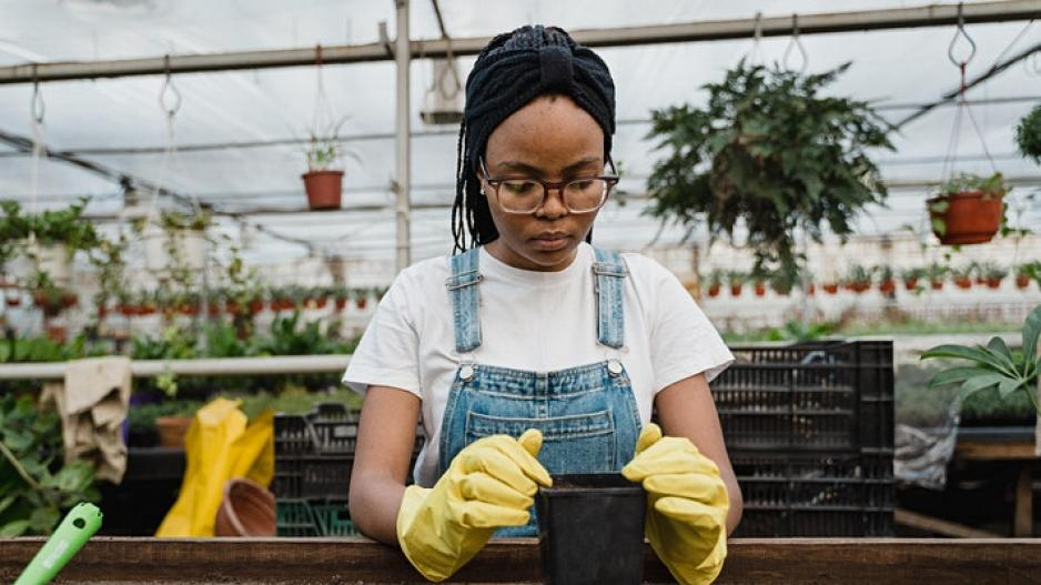 A woman in a greenhouse working with potting soil.