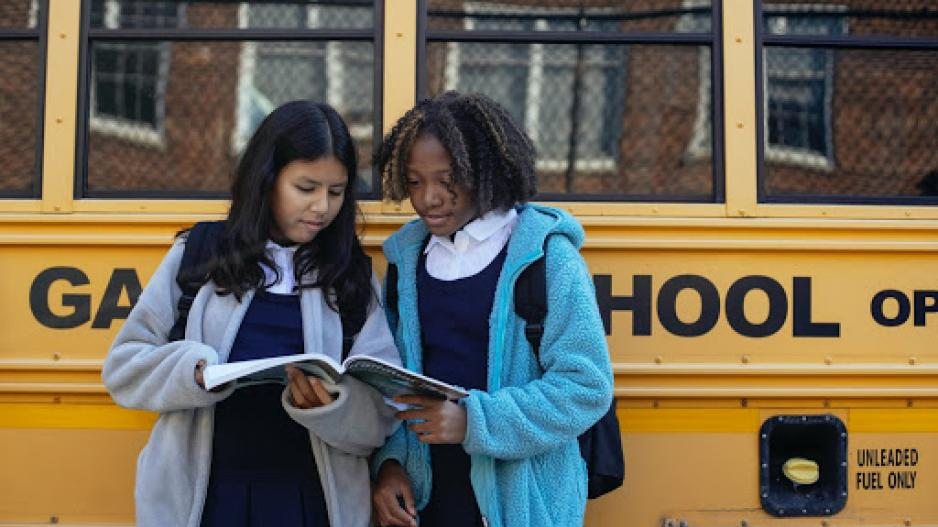 Two girls hold a textbook and look at the pages as they stand in front of a school bus