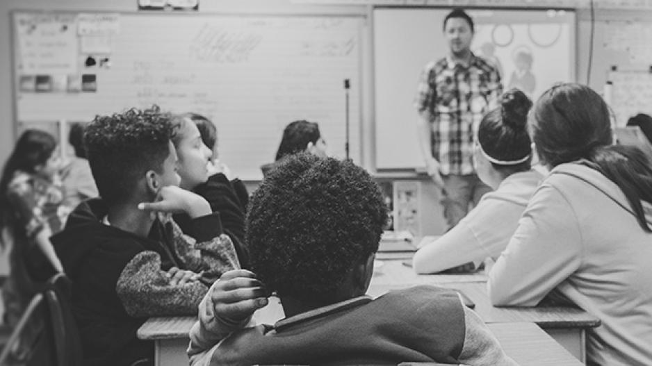 A black and white photo of a class of young teenage students looking at their teacher, who stands in front of an out of focus dry erase board