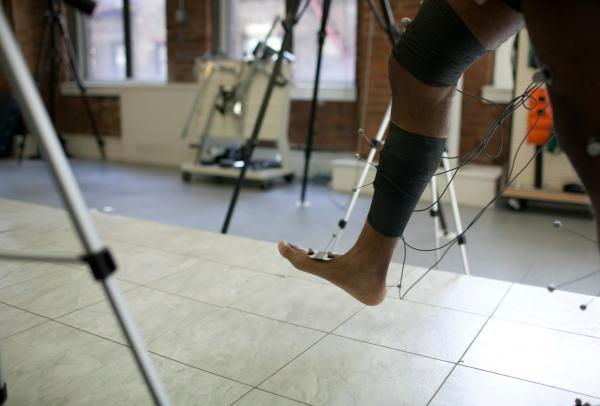 A person tests their walking using physical therapy equipment