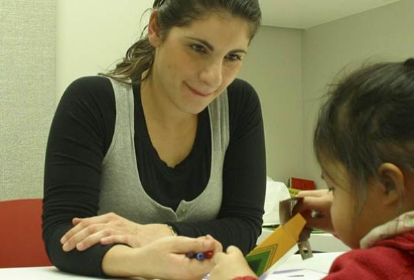 NYU Student working with a young child