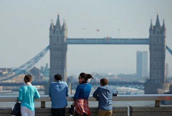 Four people standing facing the London Bridge.