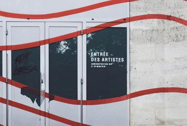 "A wall with red squiggles painted over it and a doorway reading ""Entree Des Artistes"""