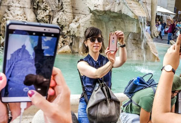 multiple tourists taking smart phone pictures