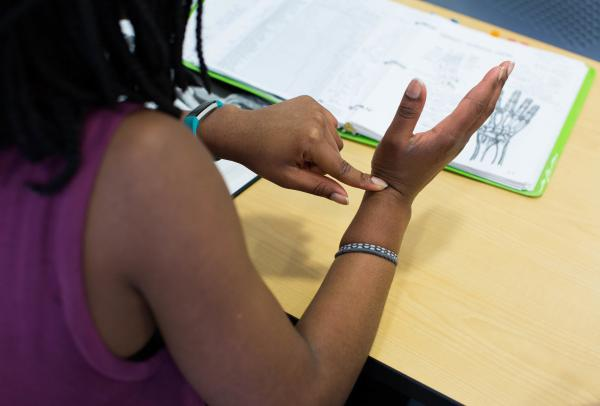 A student touching their wrist based on a diagram in a binder in front of them.