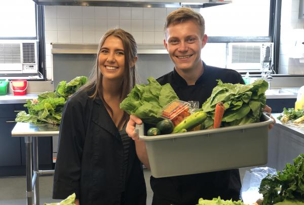 Two students holding a bucket of vegetables.