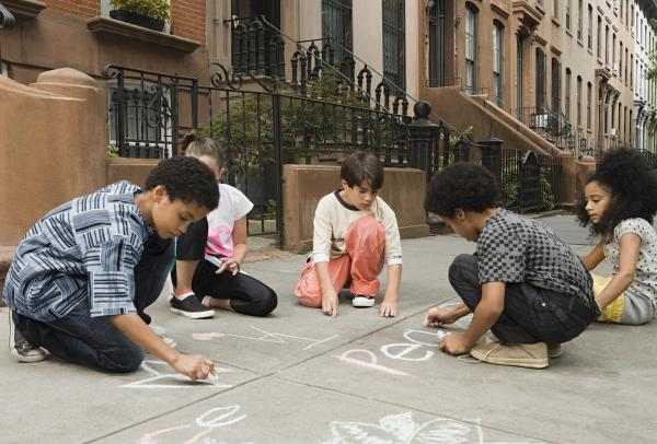Five children drawing on sidewalk with chalk