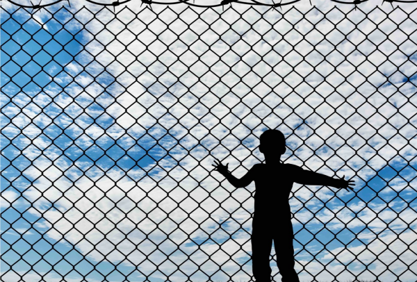 Silhouette of child behind a fence