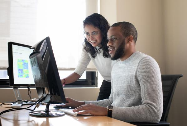 Two students looking at something on a computer