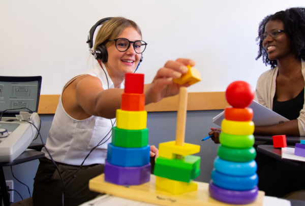 Students using audiology equipment and rainbow colored blocks.
