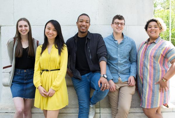 Five Steinhardt students leaning against the Washington Square Arch