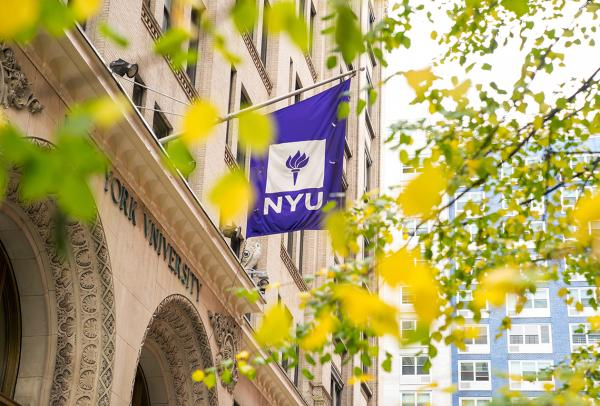 NYU flag on building with fall foliage in the foreground