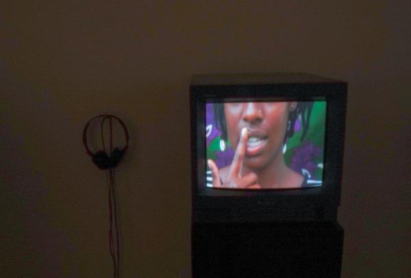 TV with image of face and mouth in the dark with headphones on wall.