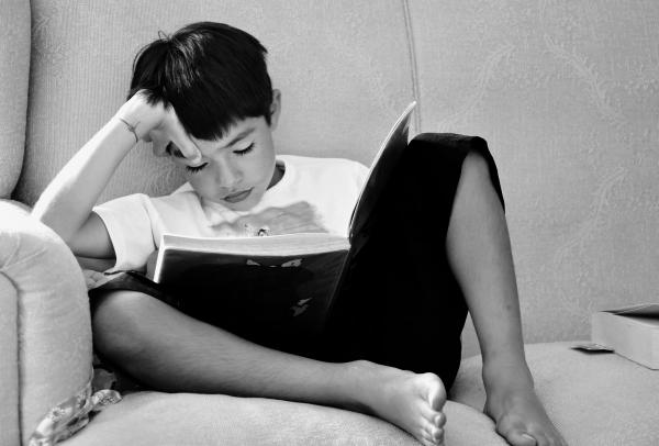 A child sitting on a couch and reading a book with his hand on his forehead