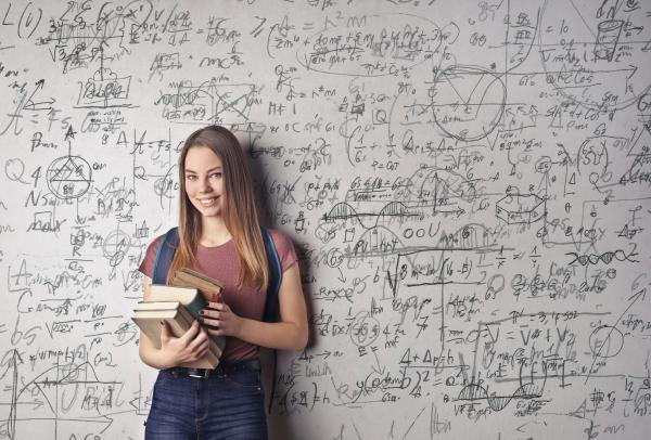 A young woman holding books standing in front of a dry erase board covered in math equations