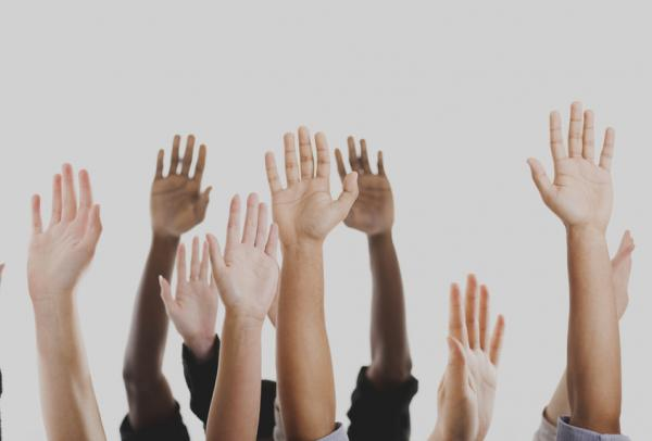 Raised hands of various skin shades.