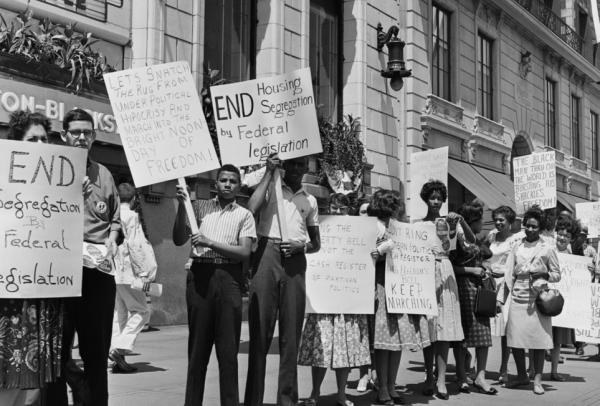 A group of mostly black protestors hold up protest signs demanding civil rights