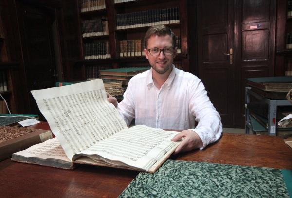 John Wilson looking at a musical score.