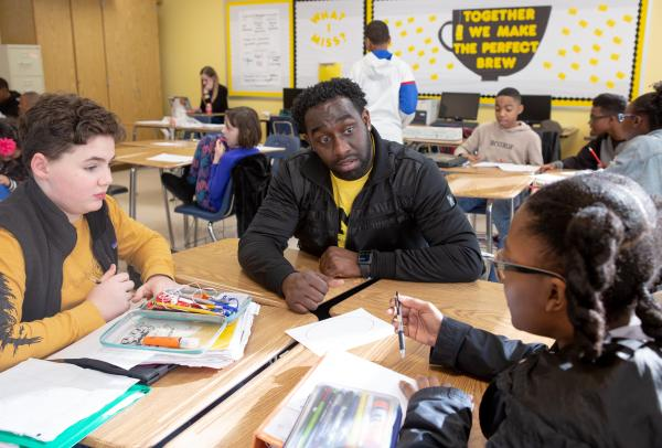 A black teacher works with a white student and a black student in a small group