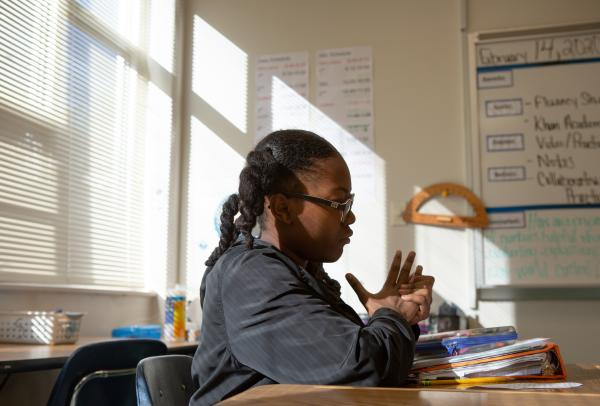 A Black girls sits alone in a classroom staring down at her assignment